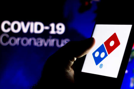 April 8, 2020, Brazil. In this photo illustration the Dominos Pizza logo seen displayed on a smartphone with a computer model of the COVID-19 coronavirus in the background. Editorial
