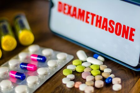 In this photo illustration pharmaceutical pills are seen displayed on a table with a Dexamethasone inscription on the background. Medically corticoid is used to treat COVID-19 (coronavirus)