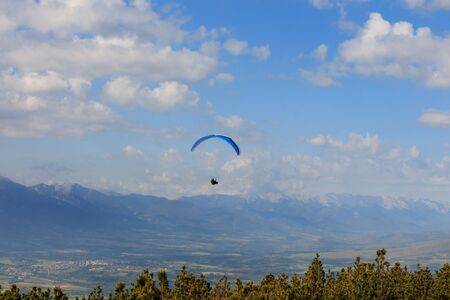 Paragliding flying through the green meadows