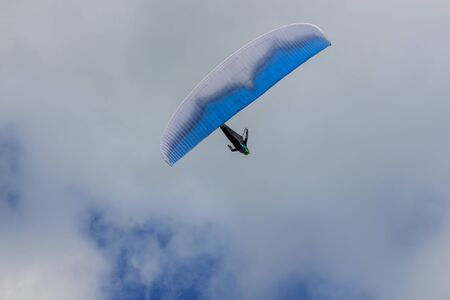 Paragliding flying through the green meadows
