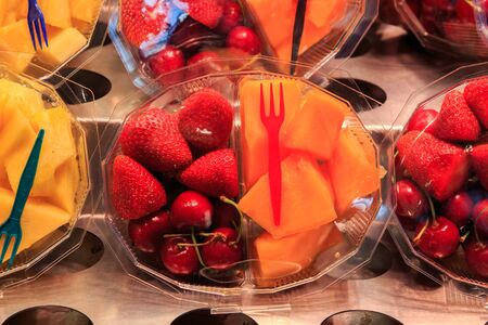 Strawberries, cherries and peach in a plastic basket with a fork Imagens