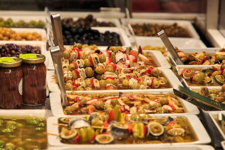 Skewers of olives and anchovies in a market stall in La Boqueria, Barcelona Imagens