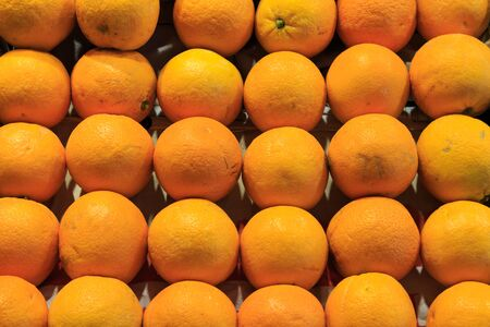 Group of fresh oranges ordered in a box put up for sale at the Boqueria market. Food concept Foto de archivo
