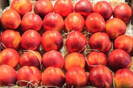 Group of fresh nectarines ordered in a box put up for sale in the Boqueria market. Food concept