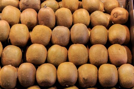 Group of fresh kiwi fruit ordered in a box put up for sale in the Boqueria market. Food concept Imagens