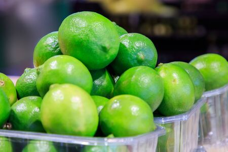Small lime lemons in plastic bowls put up for sale at the Boqueria market. Food concept