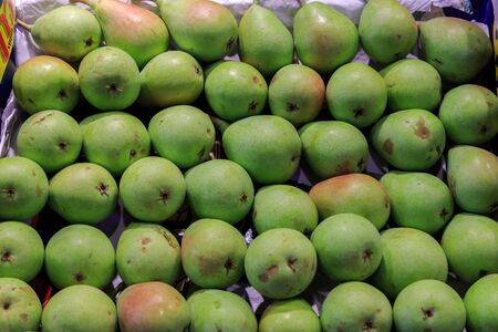 Group of fresh green pears ordered in a box put up for sale at the Boqueria market. Food concept Foto de archivo