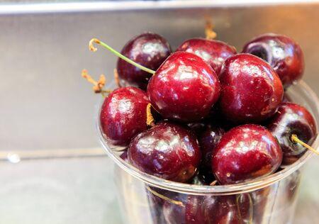 Red cherries in a plastic vase in the Boqueria Market. Food concept