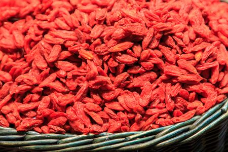 Pile of Goji berries seeds in wicker basket at the Boqueria Market. Food concept