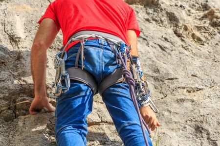 Climber hanging with express tape on his safety harness