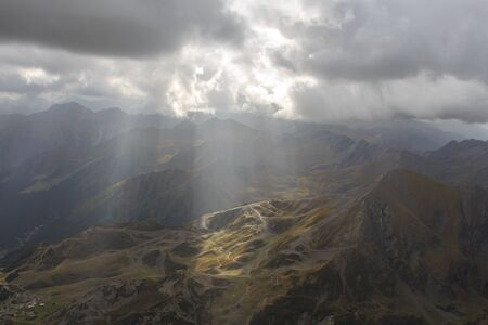 Sunbeams passing clouds and are reflected in the green mountains from the Lentilla Peak in France