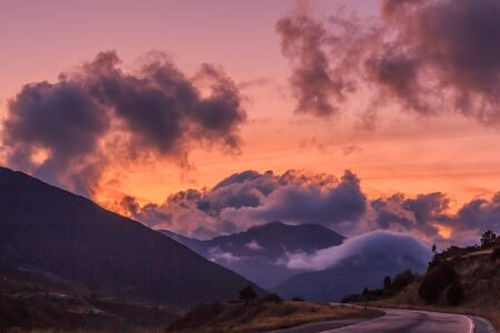 Reddish sunset with big clouds and road