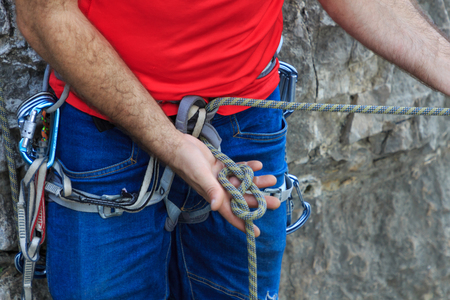 Climber with safety harness making knot 8 Editorial