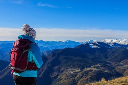 Girl with hat and backpack looking at snowy mountains.Concept people Foto de archivo