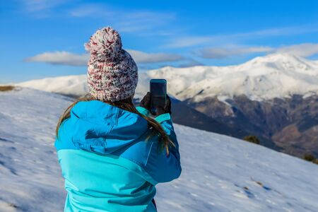 Young blonde girl with hat and blue jacket and phone in the snowy mountain.Technology concept Foto de archivo