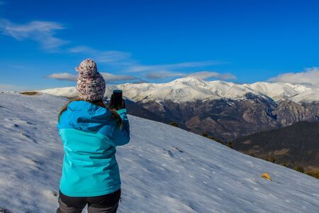 Young blonde girl with hat and blue jacket and phone in the snowy mountain.Technology concept Imagens