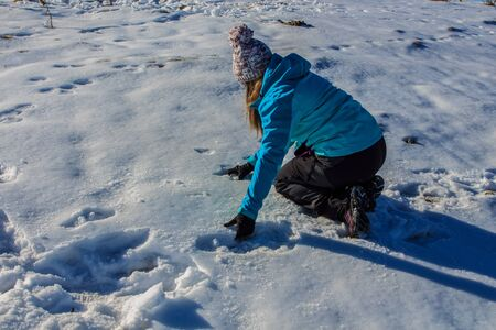 Girl with hat catching snow from the ground on the mountain.Concept people Imagens