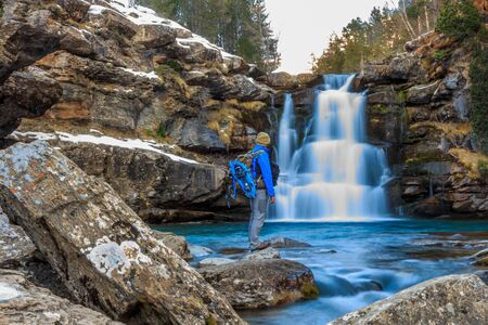 Mountaineer boy in front of waterfall with silk effect.Freestyle concept Foto de archivo