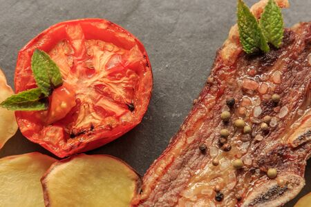 Grilled steak detail with legs and tomato on stone plate. American food concept Foto de archivo