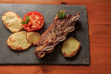 Grilled steak with legs and tomato on stone plate with wooden table. American food concept