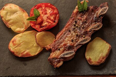 Grilled steak with legs and tomato on stone plate. American food concept Foto de archivo
