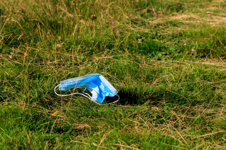 Used surgical face mask lying on the mountain grass. COVID-19 concept