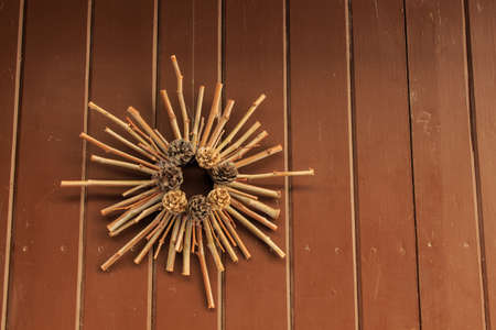 Christmas decoration hanging on exterior door with pine cones and wooden sticks. Christmas concept