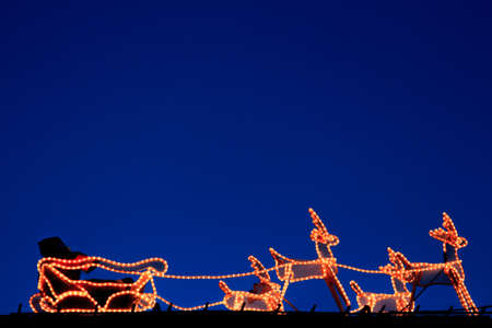 Santa Claus and reindeer formed by lights with blue sky background. Christmas concept Foto de archivo