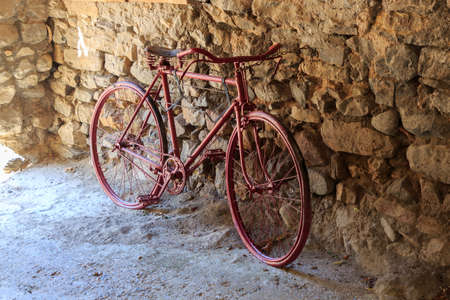 Red old bicycle leaning on stone wall.Vehicle concept