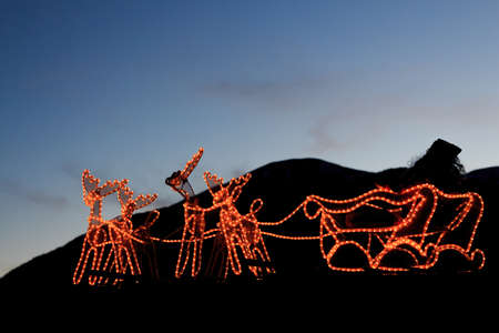 Santa Claus and reindeer formed by lights with mountains in the background. Christmas concept Foto de archivo