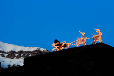 Santa Claus and reindeer formed by lights with snowy mountains in the background. Christmas concept