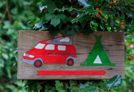 Wooden information sign drawn of a van and tent nailed to a tree. Indicative concept Foto de archivo