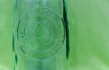 Recyclable transparent glass bottle with green background. Material recycling concept