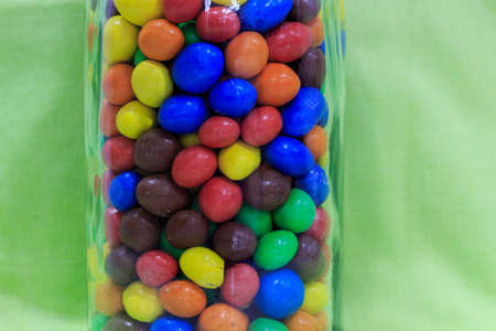 Transparent glass bottle filled with colored chocolate balls with green background. Sweets for kids concept
