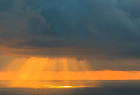 Sunbeams in the sea breaking through the clouds.Concept elements of Nature