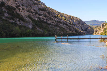 Panoramic view of wooden jetty in transparent water lake between mountains Foto de archivo