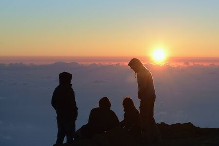 Silhouettes of mountaineers in sunset background