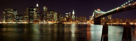 Night panorama of Brooklyn Bridge in front of the Manhattan skyline in New York. Stock Photo