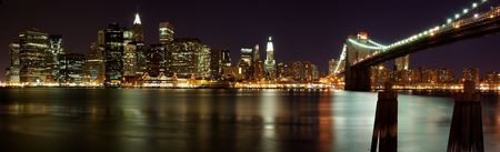 Night panorama of Brooklyn Bridge in front of the Manhattan skyline in New York. photo