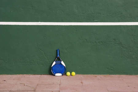 point and shoot: Two yellow tennis balls and a racket near the tennis wall Stock Photo