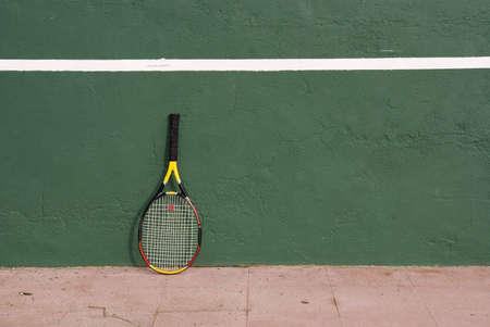 A tennis racket near the tennis wall
