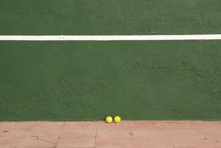 Two yellow tennis balls near the tennis wall Stock Photo
