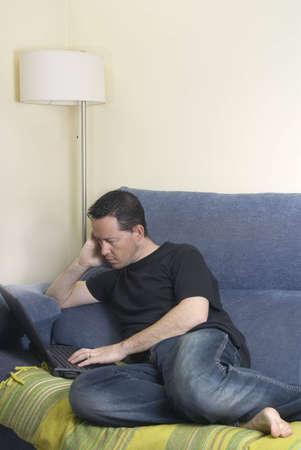net surfing: Teen su un divano di navigare in rete con il suo computer portatile