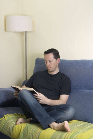 Teen on a sofa reading a book photo