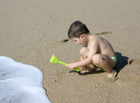 A kid playing on the beach sand