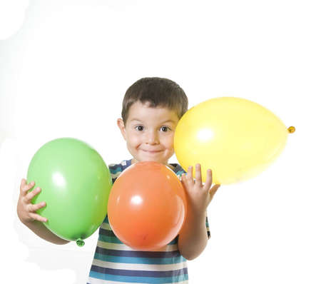 An Adorable Kid playing with coloured baloons isolated on white Stock Photo