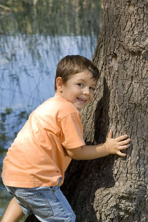 Kid smiling while he is climbing the tree