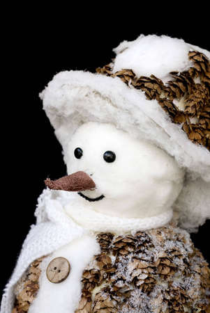 smiling snowman toy dressed in scarf and cap isolated on black background