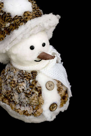 smiling snowman toy dressed in scarf and cap isolated on black background Stock Photo - 5681068