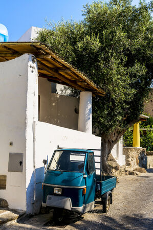 Tiny truck  car in Italy parked on the side of a road. Frontal view Stock Photo